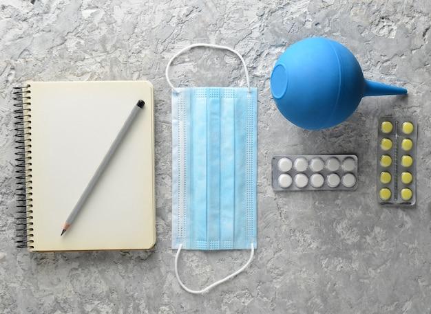 Medische apparatuur op een grijze concrete achtergrond. klysma, pillen, notitieblok. medisch concept, bovenaanzicht, plat lag stijl