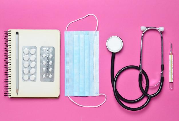 Medische apparatuur op een roze achtergrond. blarenpillen, blocnote, stethoscoop, thermometer. medisch concept, bovenaanzicht, plat lag stijl