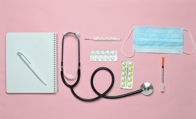 Medische apparatuur op een roze pastel achtergrond. blarenpillen, blocnote, stethoscoop, thermometer, manometer. medisch concept, bovenaanzicht, plat lag stijl