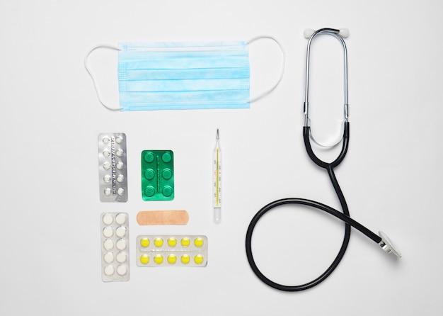 Medische apparatuur op een witte achtergrond. stethoscoop, tablet, thermometer. medisch concept, bovenaanzicht, plat lag stijl