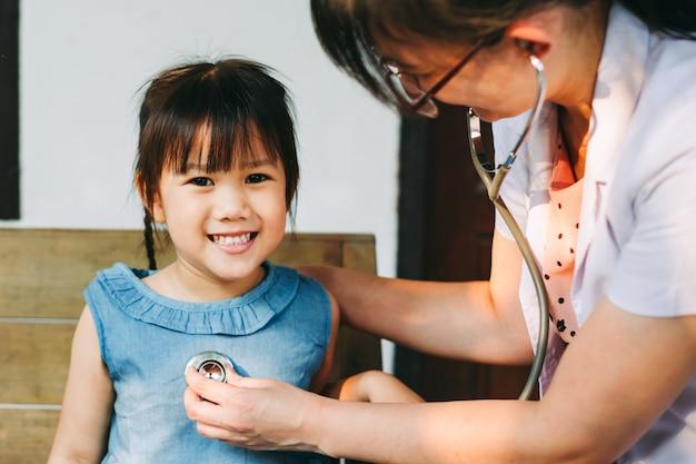Medische arts die stethoscoop met behulp van die ademhalingsgeluid van jong geitje controleert. ziekte en gezondheid concept.