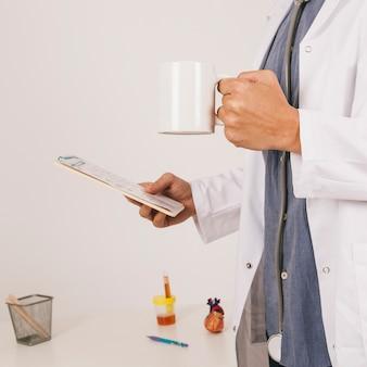 Medische arts met ipad en koffiemok
