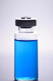 Medische blauwe injectieflacon met oplossing voor injectie op witte muur