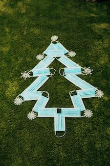 Medische blauwe maskers gemaakt kerstboom op een groene achtergrond