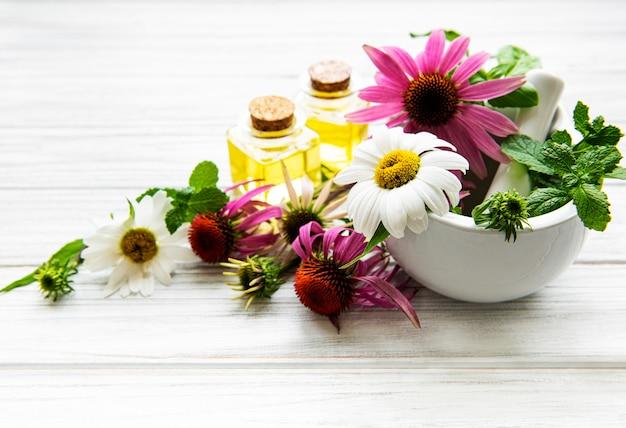 Medische bloemen en planten in mortel en etherische oliën op een witte houten tafel