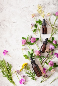 Medische bloemen kruiden etherische oliën in flessen. alternatief medicijn. klaver duizendblad boerenwormkruid