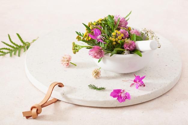 Medische bloemenkruiden in mortel. alternatief medicijn. klaver duizendblad boerenwormkruid
