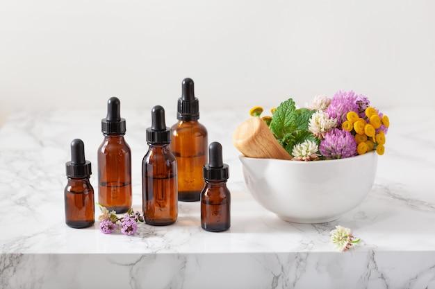 Medische bloemenkruiden in mortel etherische oliën in flessen. alternatief medicijn. klaver duizendblad boerenwormkruid