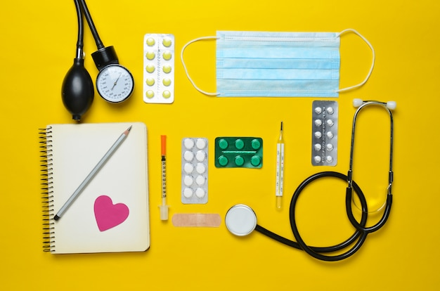 Medische cardiologische apparatuur op een gele achtergrond. blarenpillen, notebook, stethoscoop, spuit, thermometer, manometer. medisch concept, bovenaanzicht, plat lag stijl