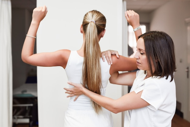 Medische controle op de schouder in een fysiotherapie centrum.
