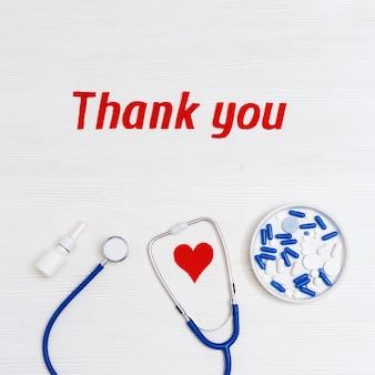 Medische elementen op tafel met 'dank u' tekst