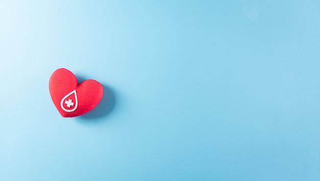 Medische en donorconcepten dokterstethoscoop en een handgemaakt rood hart met een teken of symbool van bloeddonatie