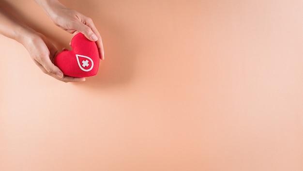 Medische en donorconcepten hand met een handgemaakt rood hart een teken of symbool van bloeddonatie voor wereldbloeddonordag