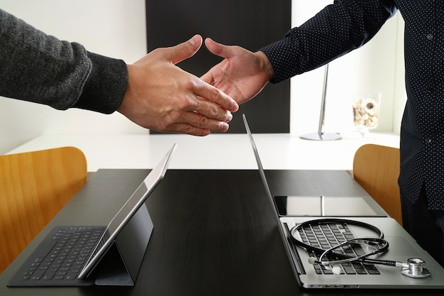 Medische en gezondheidszorg concept, arts en patiënt schudden handen in moderne kantoor in het ziekenhuis