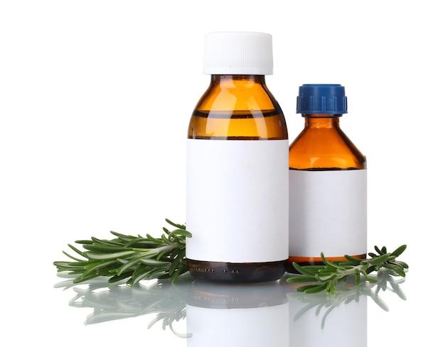 Medische flessen en verse groene rozemarijn op wit wordt geïsoleerd