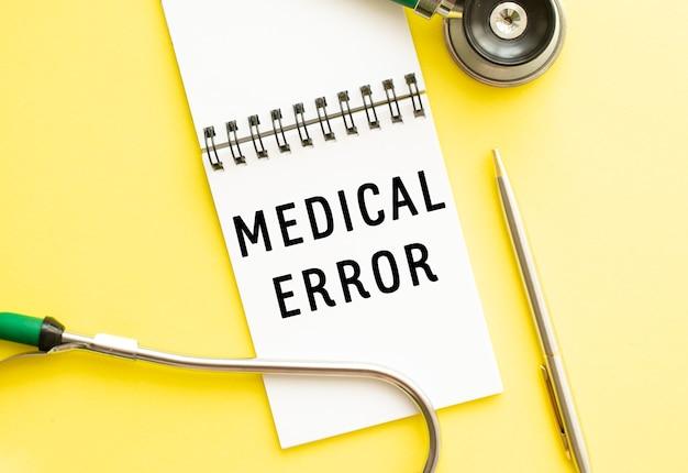 Medische fout is geschreven in een notitieboekje op een kleurentafel