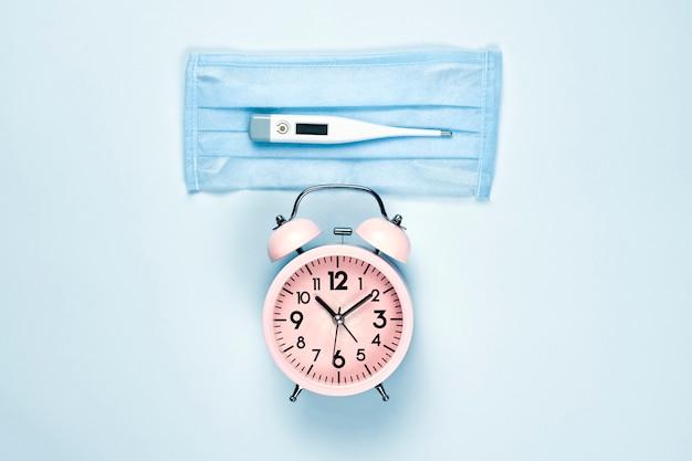 Medische gezichtsmasker en thermometer op heldere blauwe achtergrond