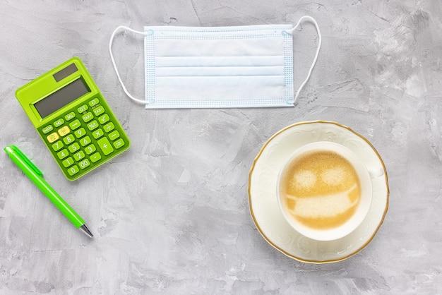 Medische gezichtsmasker rekenmachine pen kopje koffie