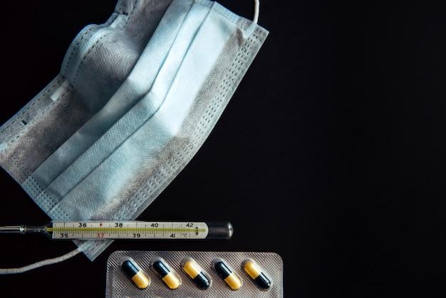 Medische gezichtsmasker, thermometer en capsules in blisterverpakking, close-up. thermometer en geneeskunde op zwarte achtergrond. epidemie, coronavirus, influenza, acute luchtwegaandoeningen.