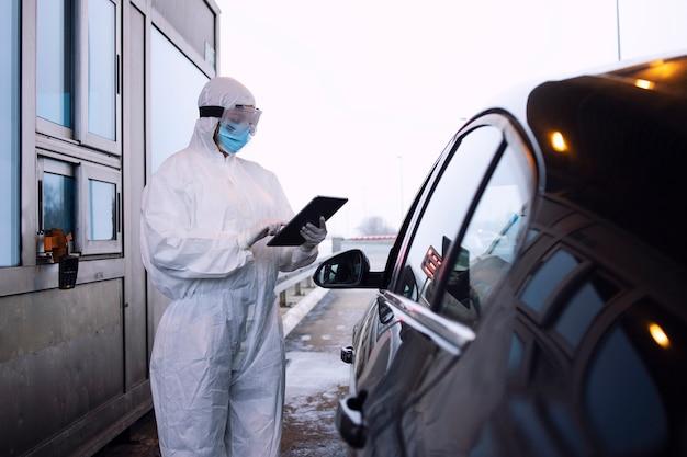 Medische gezondheidswerker in beschermend wit pak controleert passagiers en pcr-test bij grensovergang vanwege wereldwijde coronaviruspandemie.