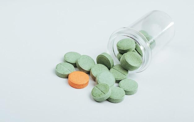 Medische groene en één oranje pil voor de behandeling en gezondheidszorg op een witte achtergrond