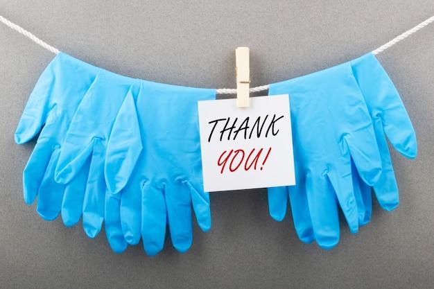 Medische handschoenen met de inscriptie bedankt. dankbaarheid aan artsen tijdens covid-concept