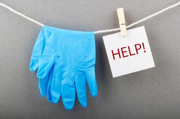 Medische handschoenen met de inscriptie help concept van covid en coronavirus