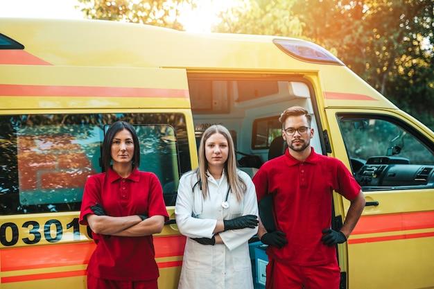 Medische hulpdiensten man en vrouw staan en poseren voor ambulance auto.