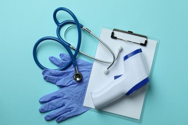 Medische hulpmiddelen en thermometerkanon op blauw