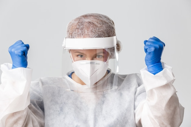 Medische hulpverleners, covid-19 pandemie, coronavirus-concept. close-up van succesvolle en vrolijke vrouwelijke arts, verpleegster in persoonlijke beschermingsmiddelen vuistpomp, moedigt zichzelf aan, blijft optimistisch.