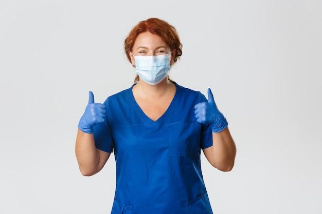 Medische hulpverleners, covid-19 pandemie, coronavirus-concept. gelukkig lachend verpleegster, vrouwelijke arts van middelbare leeftijd in scrubs, medisch masker en handschoenen met thumbs-up in goedkeuring, kliniek aanbevelen.