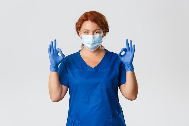 Medische hulpverleners, covid-19 pandemie, coronavirus-concept. zelfverzekerde glimlachende roodharige arts, vrouwelijke verpleegster in medisch masker, handschoenen, ok gebaar tonen, zorgen voor veilige controle tijdens virusuitbraak.