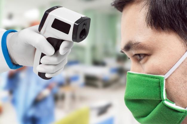 Medische infraroodthermometer in een hand van de arts die de temperatuur van de aziatische mannelijke patiënt meet, draagt een beschermend chirurgisch masker op het gezicht, corona-virus, covid-19.