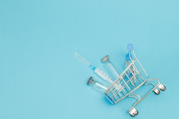 Medische injectie in het winkelwagentje op blauw.