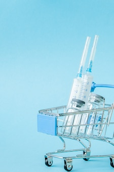Medische injectie in winkelwagentje op blauwe achtergrond.