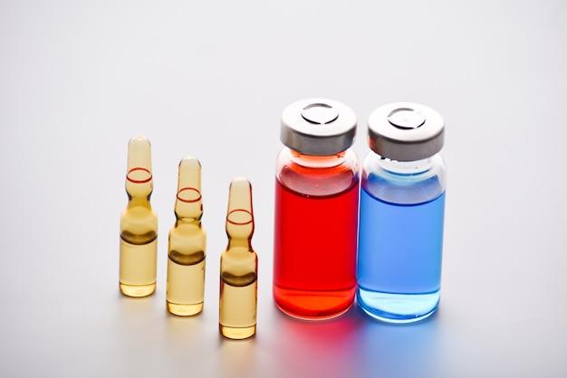 Medische injectieflacons en ampullen voor injectie. medicijnen en ziektebehandeling. blauwe en rode flesjes en ampullen. farmacologie en wetenschap. kopieer ruimte.