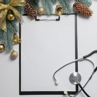 Medische kerst plat leggen met klembord en stethoscoop is omlijst met nieuwjaarsdecor.