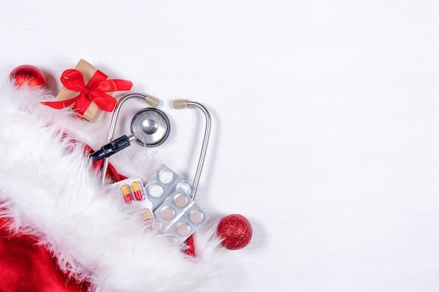 Medische kerstkaart met pillen, huidige giftdoos, stethoscoop op wit