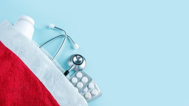 Medische kerstmissamenstelling met pillen, potje vitaminen en stethoscoop in de rode hoed van de kerstman