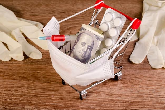 Medische masker, spuit, tabletten, honderd dollar en medische handschoenen ligt in speelgoed winkelwagen.