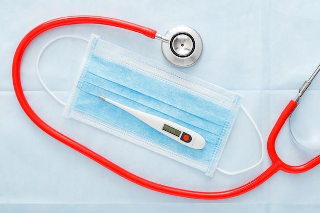 Medische masker thermometer rode stethoscoop, chirurgische bescherming gezichtsmasker op blauwe achtergrond. professionele apparatuur voor artsen. gezondheidszorg medisch concept. coronovirus covid-19-preventie plat leggen