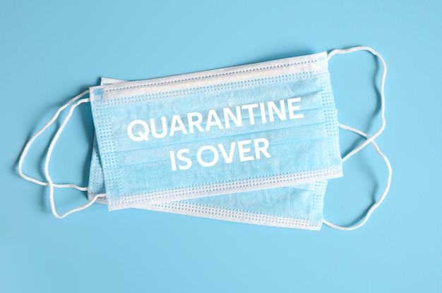 Medische maskers blauwe kleur voor bescherming tegen bacteriën op een blauwe achtergrond en tekst quarantaine is meer dan ofl lettertype
