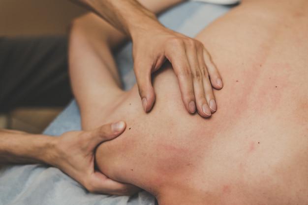 Medische massage van de wervelkolom. masseur masseert een tiener in een kliniek