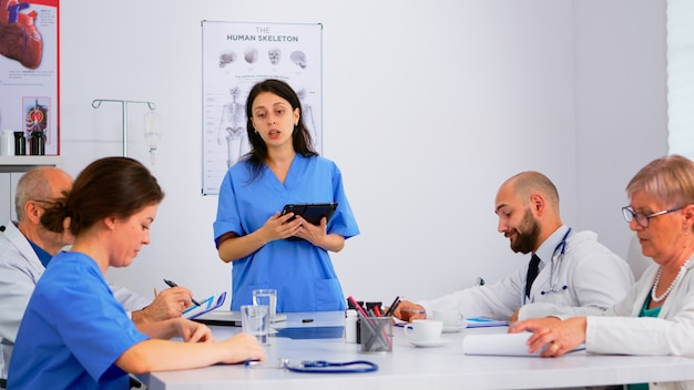 Medische mensen ontmoeten en plannen aandeelhouders in het ziekenhuiskantoor aan de balie. artsen en verpleegkundigen brainstormen samen over ideeën, artsen diagnosticeren en presenteren gegevens met behulp van tablet