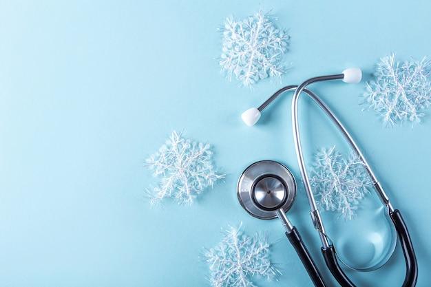 Medische nieuwjaarsamenstelling met stethoscoop en kerstmisdecoratie, kunstmatige sneeuwvlokken