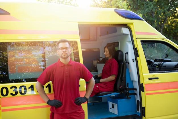 Medische noodhulp werknemer staat en poseert voor ambulance auto.