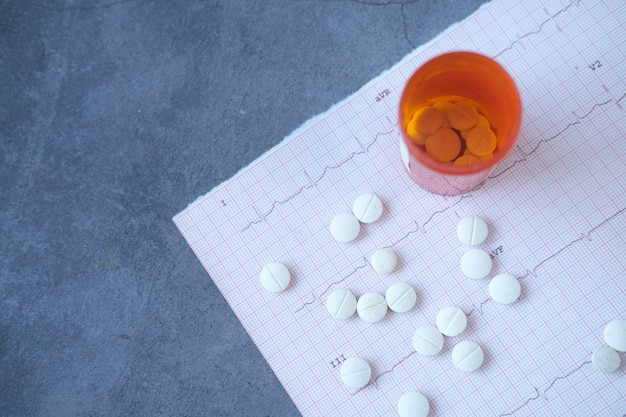 Medische pillen en container op een cardio-diagram