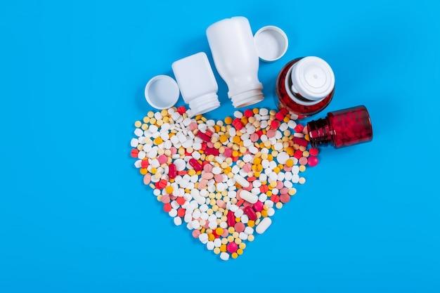 Medische pillen en tabletten die uit een drugfles morsen op blauwe achtergrond.