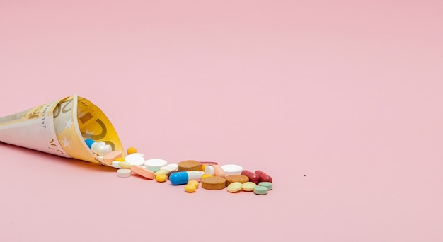 Medische pillen en tabletten in eurobankbiljettengeld als symbool van de kosten van de gezondheidszorg