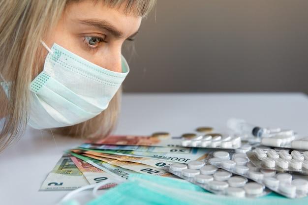 Medische pillen, eurobankbiljetten, pillen en coronavirus model met vrouw met masker